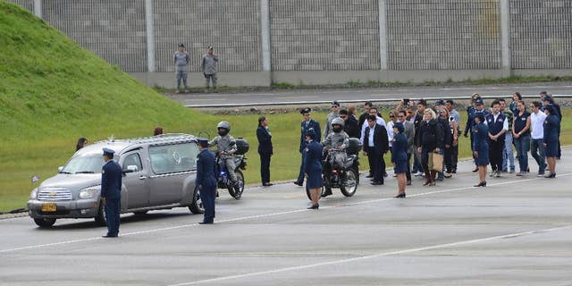 Relatives walk behind a hearse transporting a casket containing the remains of a LaMia flight crew victim to a waiting cargo plane at the military airbase in Rio Negro, Colombia, Friday, Dec. 2, 2016. An honor guard played taps early Friday as members of Colombia's military loaded the five flight crew victims of an air crash that also killed most members of a soccer team and a group of journalists, onto a cargo plane for the trip back to their native Bolivia. (AP Photo/Luis Benavides)