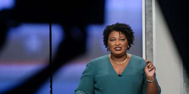Georgia Democratic gubernatorial nominee Stacey Abrams participates in a debate with Stacey Evans as a stage manager holds up a time card Sunday, May 20, 2018, in Atlanta.
