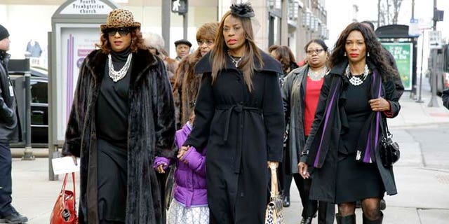 """Ernie Banks' wife Liz, second from right, walks to Chicago's Fourth Presbyterian Church for an official memorial service for Hall of Fame slugger Ernie Banks in Chicago on Saturday, Jan. 31, 2015. Banks died Friday at 83 after a heart attack, according to an attorney representing his family. Known as """"Mr. Cub,"""" Banks is remembered as much for his boundless enthusiasm despite playing on mostly losing teams as his 512 home runs and two MVP awards. (AP Photo/Nam Y. Huh)"""