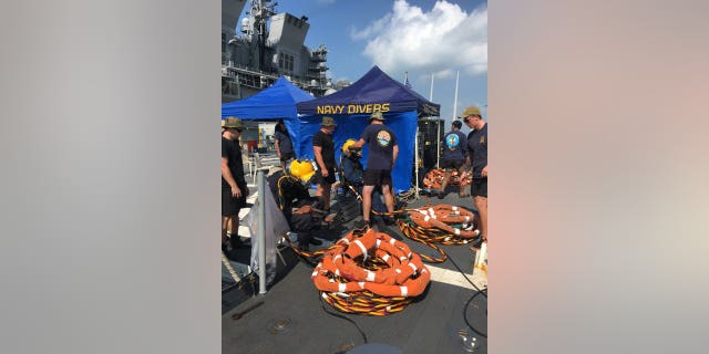 Divers search for missing sailors trapped in a warship off the coast of Singapore.