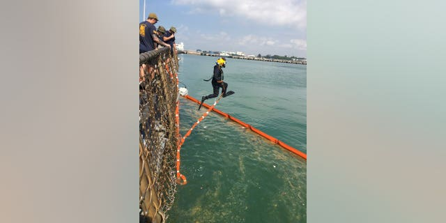Divers search for missing sailors trapped inside the USS John S. McCain.