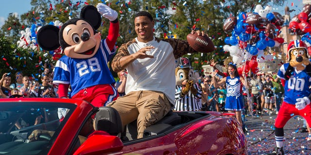 """(Feb. 3, 2014): Super Bowl XLVII MVP Malcolm Smith rides Feb. 3, 2014 with Mickey Mouse in a parade through the Magic Kingdom at Walt Disney World Resort in Lake Buena Vista, Fla. Smith, a linebacker for the Seattle Seahawks, helped lead his team to a 43-8 victory last night over the Denver Broncos in East Rutherford, N.J. After the game, Smith became the NFL's first defensive player to star in the iconic Disney Parks commercial where he proclaimed """"I'm Going to Disney World!"""" (Matt Stroshane, photographer)"""