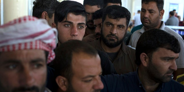 Displaced men from Mosul wait in a queue before casting their ballot in the parliamentary elections at a polling site in a camp for displaced people in Baharka, Iraq, Saturday, May 12, 2018.