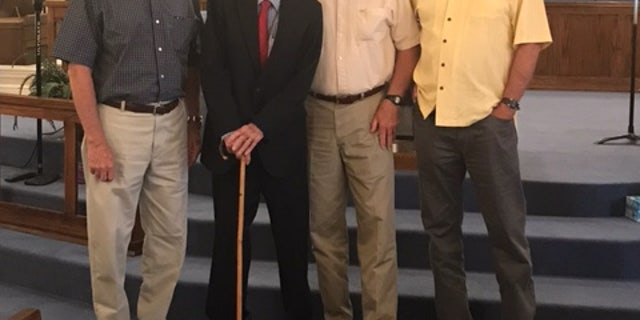 Dixon poses for a photo with his three sons.