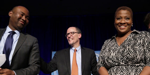 Tom Perez, center, speaks to Jamie Harrison, left, and Jehmu Green, right, in Baltimore, Maryland on February 11, 2017, during a DNC forum.