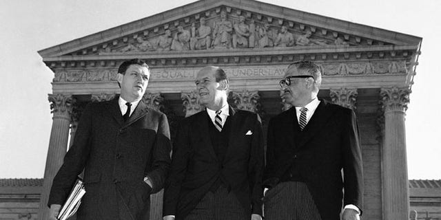 In this Jan. 17, 1966 file photo, Assistant Attorney General John Doar, left, stands with Attorney General Nicholas Katzenbach, center, and Solicitor General Thurgood Marshall as they arrive at the Supreme Court building in Washington to defend the legality of the 1965 Voting Rights Act. (AP)