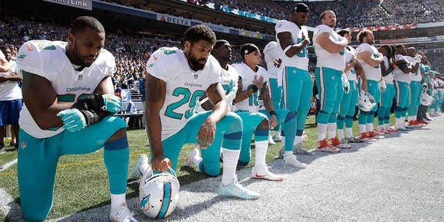 In this Sept. 11, 2017 file photo, from left, Miami Dolphins' Jelani Jenkins, Arian Foster, Michael Thomas, and Kenny Stills, kneel during the singing of the national anthem before an NFL football game against the Seattle Seahawks in Seattle.