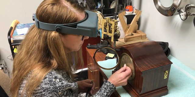 Donna Kalinkiewicz works on a clock at her workship inside her home in Birmingham, Ala. Kalinkiewicz says children need to be taught how to read analog clocks instead of just relying on digital devices to tell time.