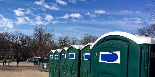 A row of portable restrooms, with the name Don's Johns covered up by blue tape, is seen on Capitol Hill in DC.