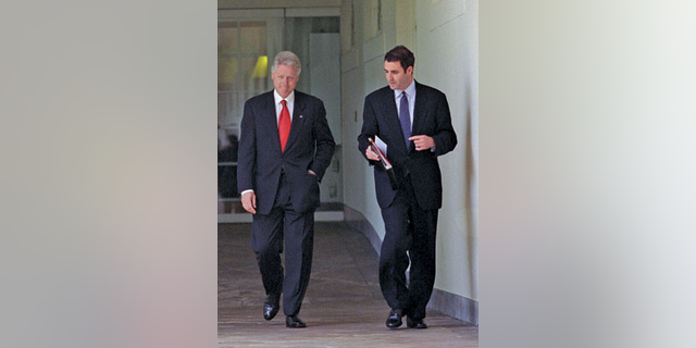 President Bill Clinton, left, walks with aide Doug Band.