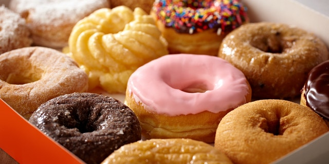 Tight shot of box containing a dozen doughnuts, shallow focus.  Professionally color corrected, exported 16 bit depth, retouched and saved for maximum image quality.