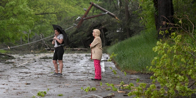 Two women look at the storm damage in Bridgewater, Conn., on Tuesday after severe storms rolled through the area.