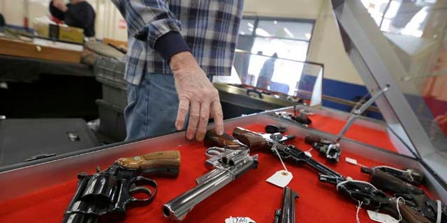Feb. 6, 2015: Gun salesman arranges handguns in a display case in advance of a show at the Arkansas State Fairgrounds in Little Rock, Ark.
