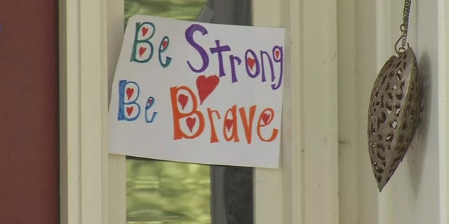 Signs of support hang for 15-year-old David Albright, who is in critical condition after was swept through an underground drainage pipe.