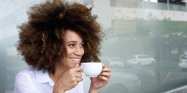 Portrait of smiling african american woman sitting with cup of coffee