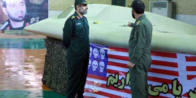 Dec. 8, 2011: This image provided by the Iranian Revolutionary Guards claims to show the chief of the aerospace division of Iran's Revolutionary Guards, Gen. Amir Ali Hajizadeh, left, listening to an unidentified colonel as he points to a US RQ-170 Sentinel drone.