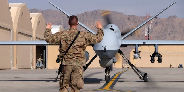 A US aviator guides an MQ-9 Reaper drone as it taxies to the runway at Kandahar Airfield, Afghanistan, in March.