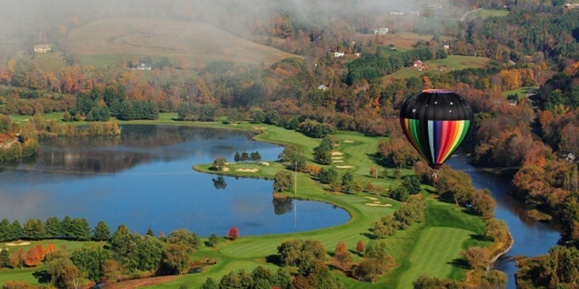 A colorful hot air balloon floating over a golf course