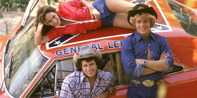 "Catherine Bach as ""Daisy,"" top, Tom Wopat as ""Luke,"" bottom left, and John Schneider, right, as ""Bo"" with The General Lee, from ""The Dukes of Hazzard."""