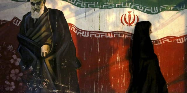 FILE - In this Nov. 2, 2013 file photo, a veiled Iranian woman walks past a mural depicting the late revolutionary founder Ayatollah Khomeini, and national Iranian flag, painted on the wall of the former U.S. Embassy, in Tehran, Iran.  Siamak Namazi, an Iranian-American businessman who advocated better ties between Iran and the U.S. reportedly has been arrested and imprisoned in Tehran, becoming the fourth U.S. citizen known to be held there at a time when hard-liners are pushing back against the country's nuclear deal with world powers. Iranian officials could not be reached for comment Friday, Oct. 30, 2015, part of the Iranian weekend, and state media did not report on Namazi's reported detention. (AP Photo/Ebrahim Noroozi)