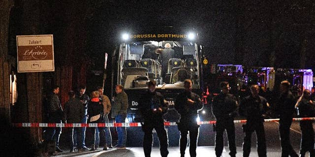 FILE - In this April 11, 2017 file photo police officers stand in front of Dortmund's damaged team bus after explosions which injured two people before the Champions League quarterfinal soccer match between Borussia Dortmund and AS Monaco in Dortmund, western Germany.   (AP Photo/Martin Meissner, file)