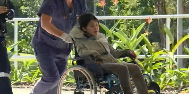 In this photo taken from the Australian Broadcasting Corporation video, South Korean backpacker Joohee Han, 25, is wheeled to a hospital after being rescued by helicopter, Thursday, June 7, 2018, in Tully, Queensland, Australia.