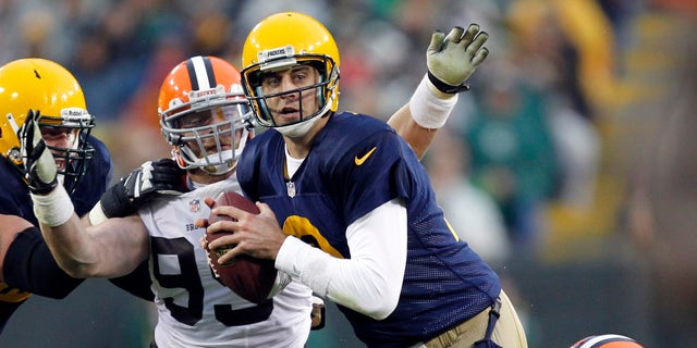 Green Bay Packers quarterback Aaron Rodgers is sacked by Cleveland Browns' Chris Owens (21) and Paul Kruger during the second half of an NFL football game Sunday, Oct. 20, 2013, in Green Bay, Wis. (AP Photo/Mike Roemer)