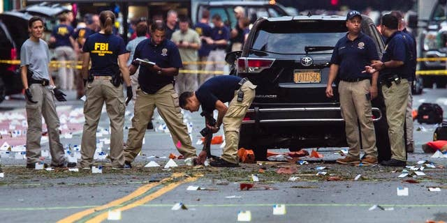 FILE - In this Sunday, Sept. 18, 2016, file photo, members of the Federal Bureau of Investigation (FBI) carry on investigations at the scene of Saturday's explosion in Manhattan's Chelsea neighborhood, New York. Investigators probing bomb blasts in New Jersey and New York believe they've identified two men who walked off with a bag abandoned by the bomber on a street as Egyptian tourists. (AP Photo/Andres Kudacki, File)