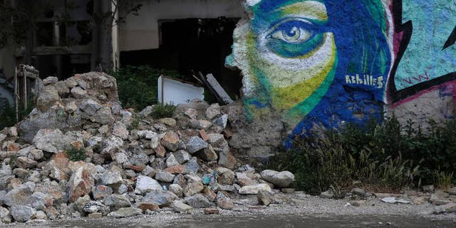 Graffiti by Greek street artist Achilles is seen on a wall of an abandoned house in central Athens, on Wednesday, April 22, 2015. Greece is running perilously short of cash amid an impasse in bailout talks with its international creditors. Eurozone finance ministers are to meet in Riga, Latvia on Friday but hopes of a deal on Greece there have diminished. (AP Photo/Petros Giannakouris)