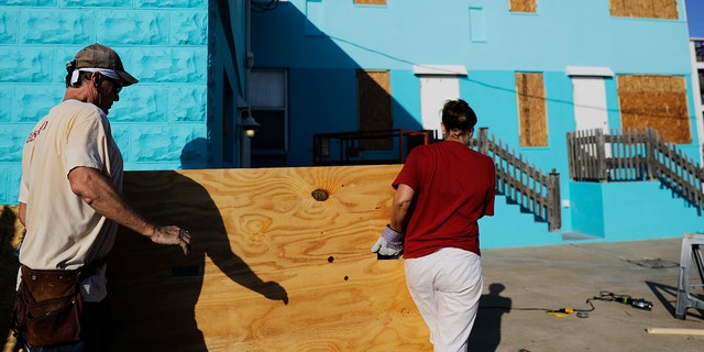 Paulita Kundid, right, and her brother Mike Kundid board up their apartment building ahead of Hurricane Irma in Daytona Beach, Fla., Friday, Sept. 8, 2017. Coastal residents around South Florida have been ordered to evacuate as the killer storm closes in on the peninsula for what could be a catastrophic blow this weekend. (AP Photo/David Goldman)