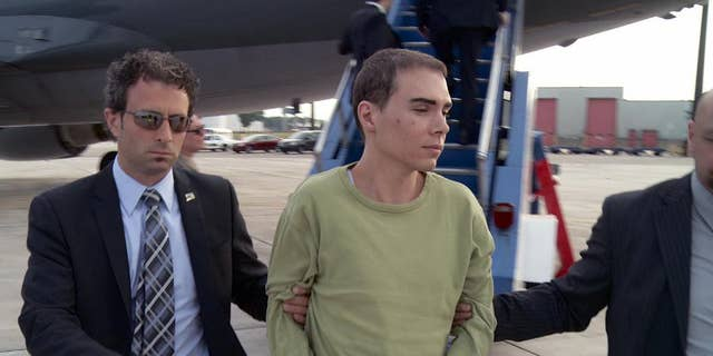 FILE - In this June 18, 2012 file photo provided by Montreal Police, Luka Rocco Magnotta is taken by police from a Canadian military plane to a waiting van in Mirabel, Quebec. Magnotta dropped his appeal Wednesday, Feb. 18, 2015 of a life sentence for killing and dismembering his Chinese lover and mailing his body parts to schools and political parties. Magnotta, 32, was sentenced to life in prison last December in the slaying and dismemberment of Jun Lin, a 33-year-old Chinese engineering student who had been living in Canada since 2011.  (AP Photo/Montreal Police)