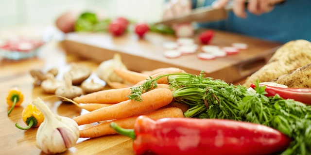 Close-up of various fresh vegetables on wooden table. Woman is chopping red radish in background. Female is preparing food. She is in domestic kitchen.