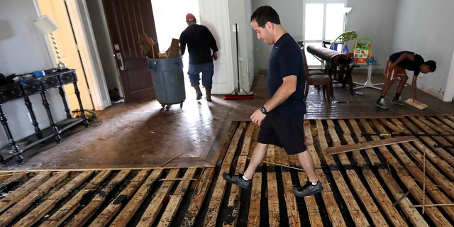 Michael Saghian walks across the living room of his home damaged by floodwaters from Tropical Storm Harvey on Wednesday, Aug. 30, 2017, in Houston. (