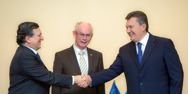 Ukraine's President Viktor Yanukovych, right, shakes hands with European Commission President Jose Manuel Barroso, left, and European Council President Herman van Rompuy, center, in Vilnius, Lithuania, Thursday, Nov 28, 2013. Van Rompuy and  Barroso met with Yanukovych hours before Thursday's start of the Vilnius summit in an attempt to cajole him into signing the long-planned association agreement as soon as possible after the two-day meeting. (AP Photo/ Mykhailo Markiv, Pool)