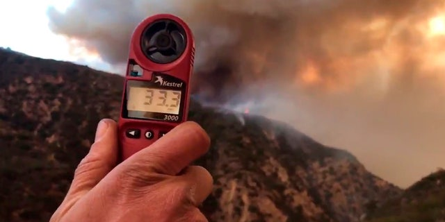 In this image from video provided by the Santa Barbara County Fire Department, a wind speed indicator held by a U.S. Forest Service fire fighter on Gibraltar Road at the W. Fork of Cold Spring Trail, shows just how fast and varied the speed of the wind is blowing down canyon. In this video it varied from 10-33 mph in Santa Barbara, Calif., Saturday, Dec. 16, 2017.