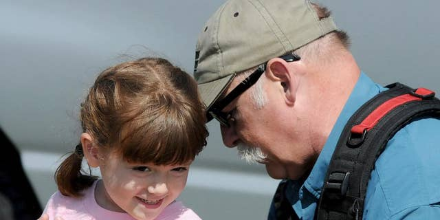 """This Friday, Sept. 19, 2015 photo shows Elizabeth """"Lizzy"""" Myers, left, being fitted for a microphone by a CBS sound man before taping a segment in Lucas, Ohio. Myers, a 5-year-old Ohio girl whose parents created a """"visual bucket list"""" for her because she's slowly going blind is going to meet Pope Francis. Steve Myers told the Mansfield News Journal on Thursday, March 24, 2016, that his daughter Elizabeth """"Lizzy"""" Myers is visiting the Vatican next week. (Jason J. Molyet/News Journal via AP) NO SALES; MANDATORY CREDIT"""