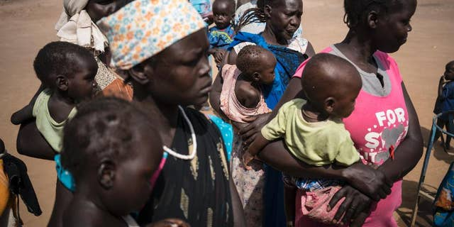 In this photo taken Monday, March 13, 2017, mothers hold their children as they wait to have them screened for malnutrition at a UNICEF-supported Outpatient Therapeutic Program in Aweil, South Sudan.