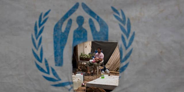 A Syrian man feeds his child behind a UNHCR plastic sheet at Ritsona refugee camp, north of Athens, which hosts about 600 refugees and migrants on Sept. 8, 2016. (AP Photo/Petros Giannakouris)