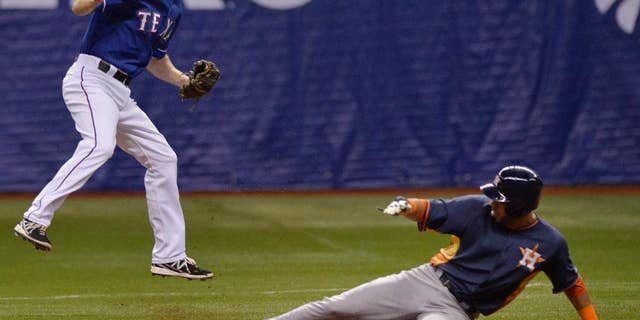 Texas Rangers' Josh Wilson, left, leaps to catch the ball as Houston Astros' Marwin Gonzalez slides safely into second base during a spring exhibition baseball game on Saturday, March 29, 2014, in San Antonio. (AP Photo/Darren Abate)