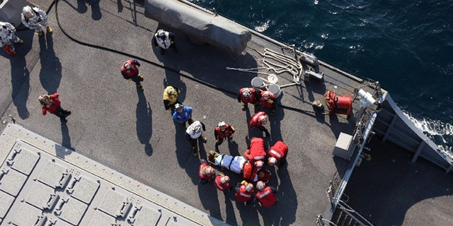 U.S. military personnel preparing to transfer an injured crew member on the USS Fitzgerald June 17.