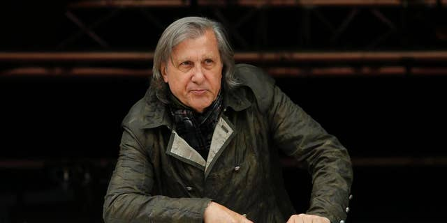 FILE - In this Monday, May 23, 2016 file picture, former Romanian tennis ace Ilie Nastase watches a match of the French Open tennis tournament at the Roland Garros stadium, in Paris, France. Ilie Nastase has received Romania's highest award, the Star of Romania, on his 70th birthday from President Klaus Iohannis for services to sport in Bucharest, Romania, Tuesday, July 19, 2016. (AP Photo/Alastair Grant, File)