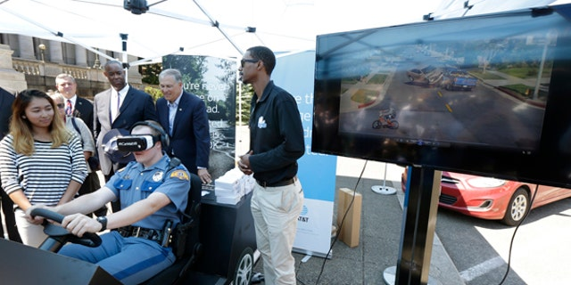 Washington State Patrol cadet Cody Fath wears goggles as he views a virtual reality depiction of several distracted driving scenarios during a press event, Monday, July 17, 2017, at the Capitol in Olympia, Wash.