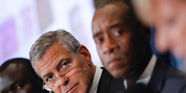 Actors George Clooney, left center, and Don Cheadle, right, during a press conference to discuss an investigation about corruption in South Sudan at the National Press Club in Washington, in 2016.