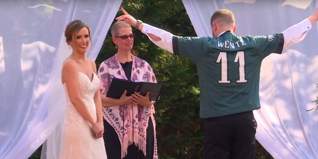 The crowd briefly cheered as Hanks donned the jersey — and the wedding DJ played the Eagles chant over the sound system.