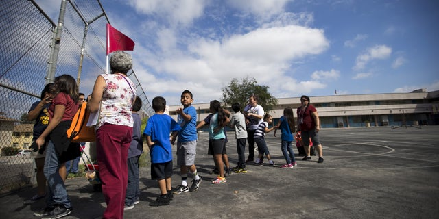 """A teacher holds a flag as she evacuates with her students during the """"Great ShakeOut"""" earthquake drill at Marlton School in Los Angeles, California October 15, 2015. (REUTERS/Mario Anzuoni)"""