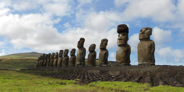 A restored statue platform with standing moai on the south coast of Rapa Nui. Note that one of the moai is adorned with a red scoria pukao. (Sean Hixon)