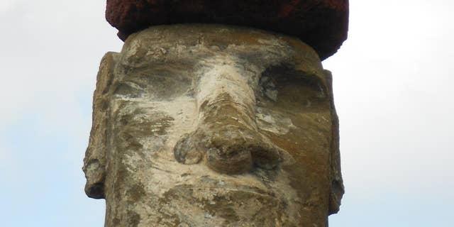 A moai adorned with a red pukao (Sean Hixon)