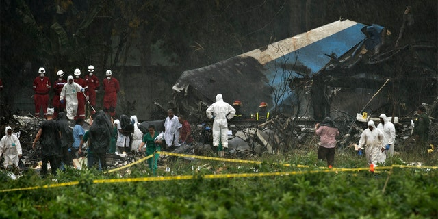 Rescue teams search through the wreckage site of a Boeing 737 that plummeted into a field with more than 100 passengers on board in Havana, Cuba on Friday.
