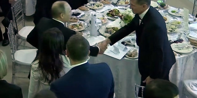 In this image made from a video taken on Dec. 10, 2015 and made available on Tuesday, Feb. 14, 2017, US President Donald Trump's former National Security Advisor Michael Flynn, right, shakes hands with Russian President Vladimir Putin, in Moscow.  (Ruptly via AP)