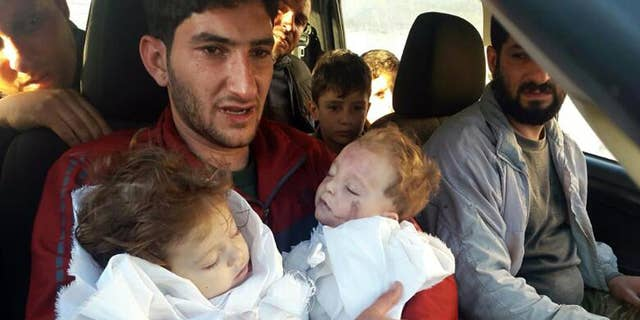 FILE -- In this Tuesday April 4, 2017 file photo, Abdel Hameed Alyousef, 29, holds his twin babies, who were killed during a suspected chemical weapons attack, in Khan Sheikhoun in the northern province of Idlib, Syria. (Alaa Alyousef via AP, File)